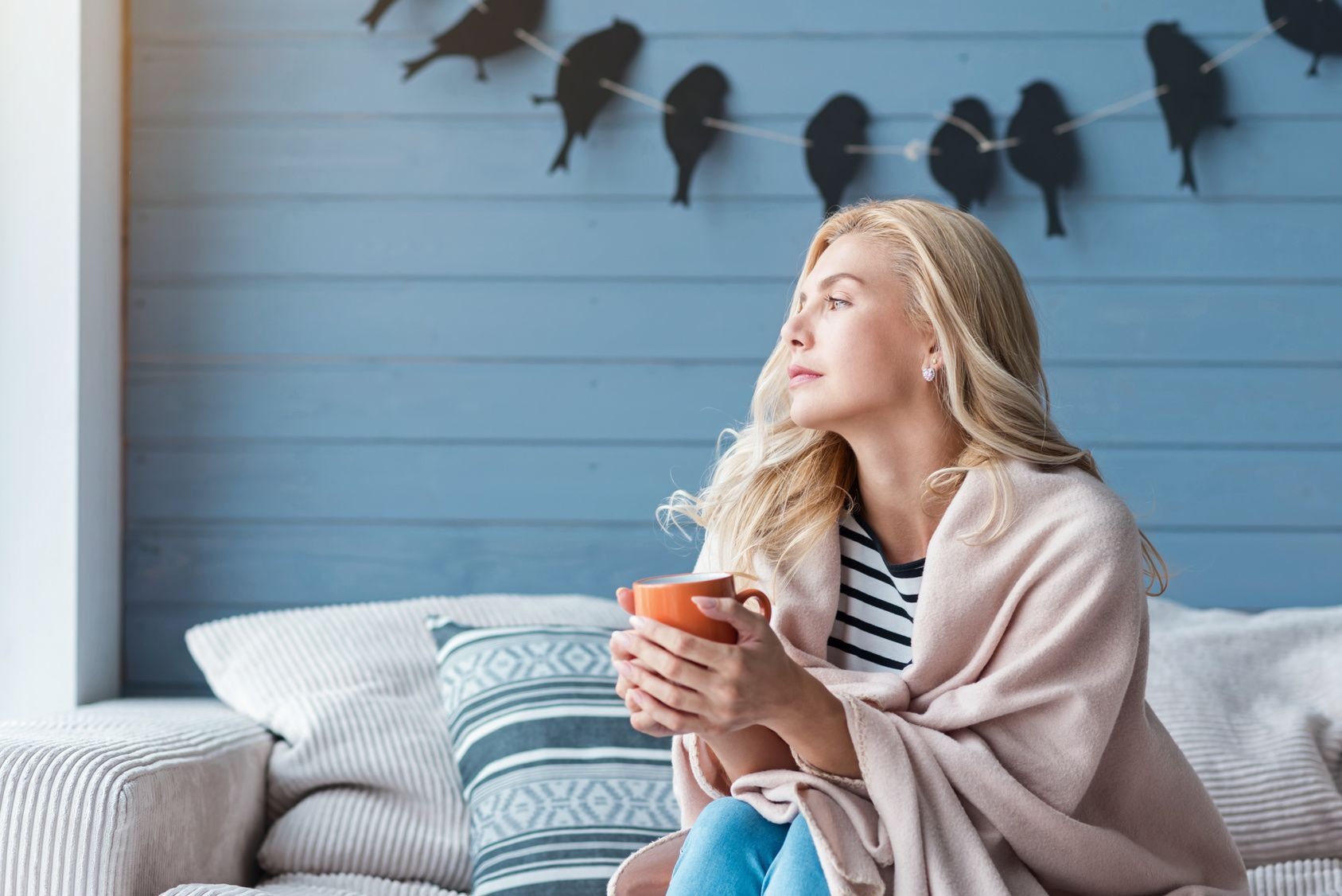 Blond woman sitting on sofa with cup